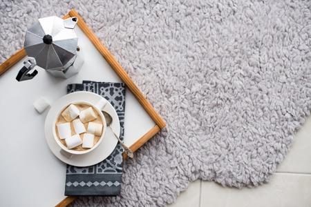 hogar cálido y acogedor. La bandeja y taza de café con malvaviscos en un piso, en el interior confortable Foto de archivo