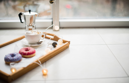 day light: Cozy home weekend, coffee and sweets in tray on floor, warm winter indoors