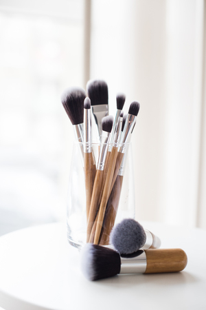 Professional makeup brushes in a glass, makeup artist's workplace