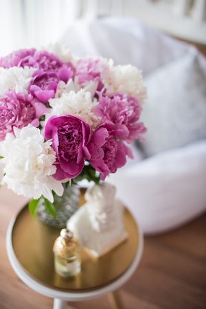 home decoration, fresh pink peonies on coffee table in white roo