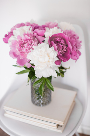 int: flowers decor, fresh peonies on designer chair in white room int