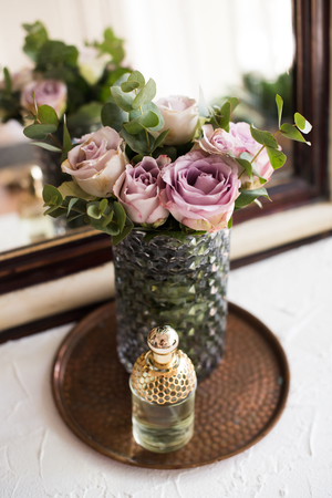 purple, mauve color fresh summer roses in vase and perfume by th