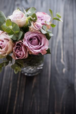 rose di estate fresche viola, color malva in vaso con tavoletta nera