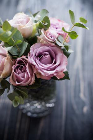 purple, mauve color fresh summer roses in vase with black tablet Reklamní fotografie
