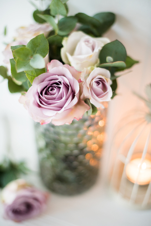 purple, mauve color fresh summer roses in vase with white wall b