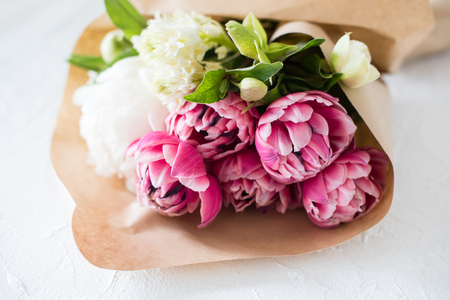 Bouquet of pink tulip flowers on table in brown paper