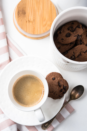 Cup of coffee and jar of chocolate cookies on breakfast table, morning meal