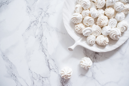 meringue cookies in in a plate on a white marble