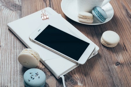 Cup of coffee, blue macaroons and smartphone on wooden table bac