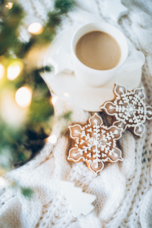 Cozy home Christmas decoration with a cup of coffee, gingerbread and white knitted blanket, new year lights bokeh closeup Zdjęcie Seryjne