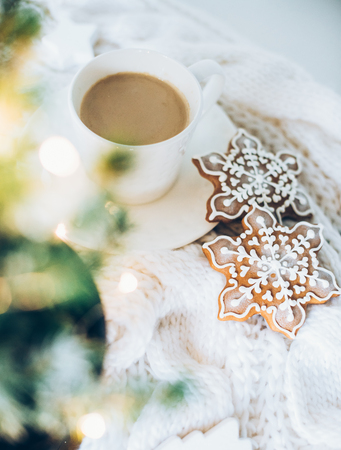 Cozy home Christmas decoration with a cup of coffee, gingerbread and white knitted blanket, new year lights bokeh closeup Фото со стока