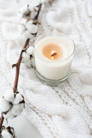 Burning hand-made candle with cotton branch on white cozy winter