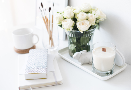 White interior decor with new hand-made candle and bouquet of roses Stock fotó