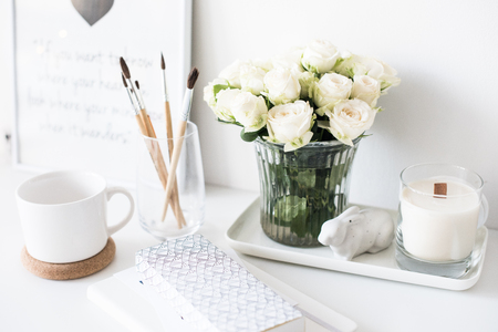 White interior decor with new hand-made candle and bouquet of fr