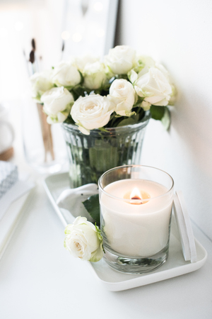 White room interior decor with burning hand-made candle and bouquet of roses