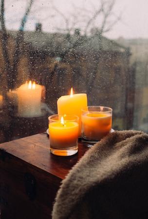 テーブルの上に3つの燃えるろうそく、居心地の良い雨の日の家