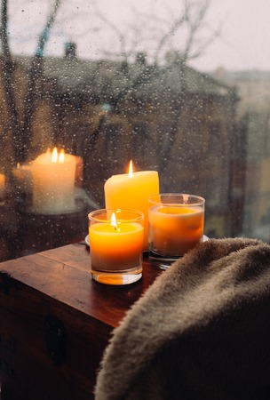 Three burning candles on table, cozy rainy day an home