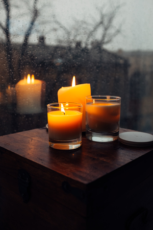 Three burning candles on table, cozy rainy day an home Stock Photo - 96710010
