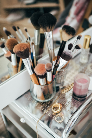 Make-up brushes and cosmetic on dressing table