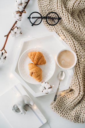 Cozy home breakfast, warm blanket, coffee and croissant on white