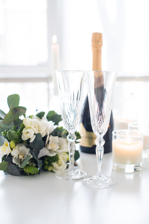 Beautiful wedding decoration with champagne and white flowers, elegant decor with crystal wine glasses on table Reklamní fotografie