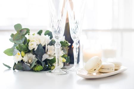 Hermosa decoración de boda con champán y flores blancas, elegante decoración con copas de vino de cristal y dulces de macarrón
