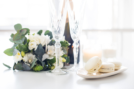 Beautiful wedding decoration with champagne and white flowers, elegant decor with crystal wine glasses and macaron sweets Archivio Fotografico