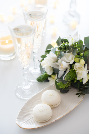 Beautiful wedding decoration with champagne and white flowers, elegant decor with crystal wine glasses and macaron sweets Reklamní fotografie