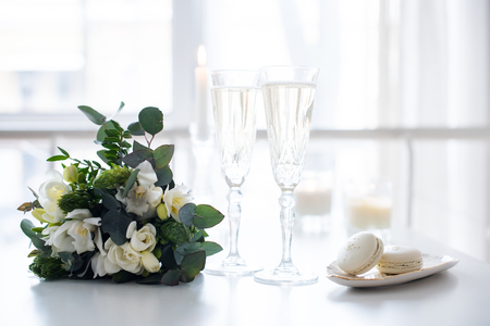 Beautiful wedding decoration with champagne and white flowers, elegant decor with crystal wine glasses and macaron sweets Banco de Imagens