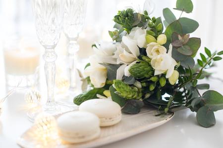 Schöne Hochzeitsdekoration mit Champagner und weißen Blumen, elegantes Dekor mit Kristallweingläsern und Macaron-Bonbons