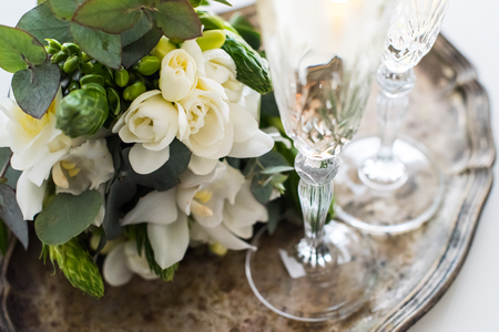 Beautiful vintage wedding decoration with champagne and white flowers, elegant decor with crystal wine glasses on ancient tray