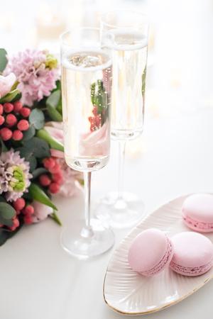 Splendida decorazione per matrimoni con champagne e fiori rosa, arredamento elegante con bicchieri di vino e dolci macaron