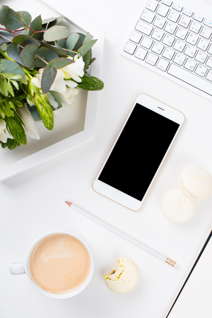 Lady bloggers work desk with fresh bouquet of flowers and macaron cakes on white table background, feminine home office workspce with coffee and smartphone mock-up