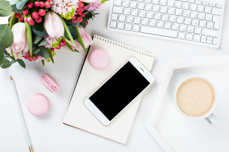 Lady bloggers work desk with pink flowers and macaron cakes on white table background, feminine home office workspce with coffee and smartphone mock-up