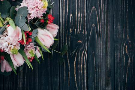 Bouquet of pink flowers on dark wooden background, festive decoration with tulips and hyacinth Banco de Imagens