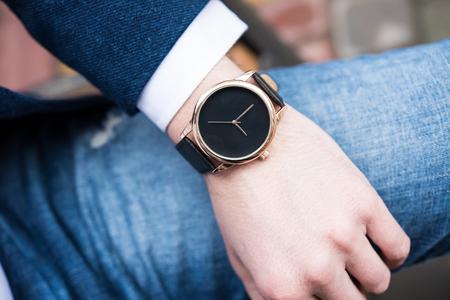 Elegancki młody człowiek z ręki z modnym zegarkiem bez marki