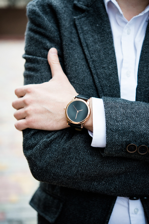 Confident man in gray jacket, elegant business mans hand with watch Stock Photo