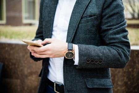 Confident man in gray jacket using smartphone, elegant business