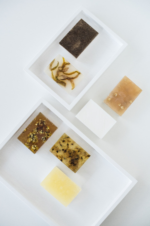 Brown and yellow handmade soap bars with honey and herbs on whit