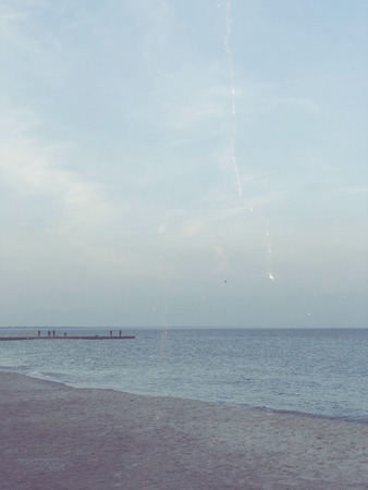 Deserted afternoon beach, calm sea 写真素材