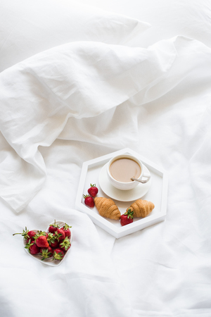 Early morning breakfast in bed, coffee and croissant with strawb 版權商用圖片