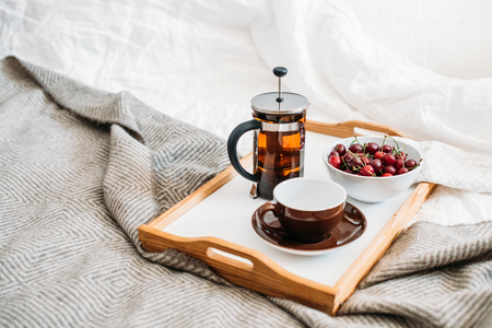 Fresh healthy vegan breakfast in bed, green tea and cherry in mo Banco de Imagens - 103370650