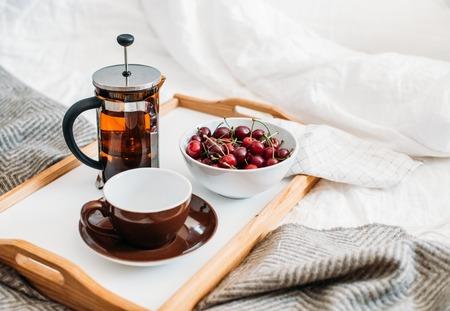 Fresh healthy vegan breakfast in bed, green tea and cherry in mo Banco de Imagens - 103370651
