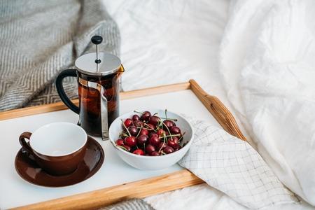 Fresh healthy vegan breakfast in bed, green tea and cherry in mo Stock Photo