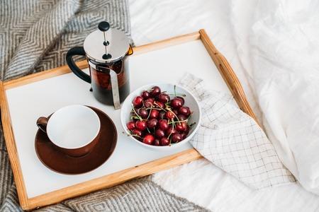 Fresh healthy vegan breakfast in bed, green tea and cherry in mo Imagens