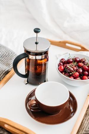 Fresh healthy vegan breakfast in bed, green tea and cherry in mo Banco de Imagens - 103370659