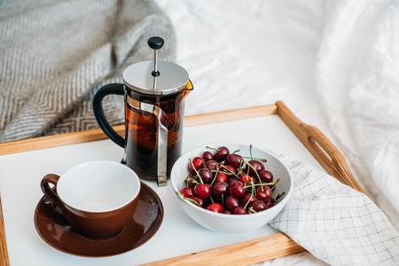Fresh healthy vegan breakfast in bed, green tea and cherry in mo Banco de Imagens - 103370660
