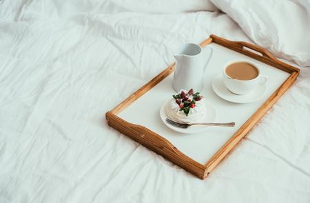 Desayuno acogedor hogar en la cama en el interior del dormitorio blanco Foto de archivo - 103142319
