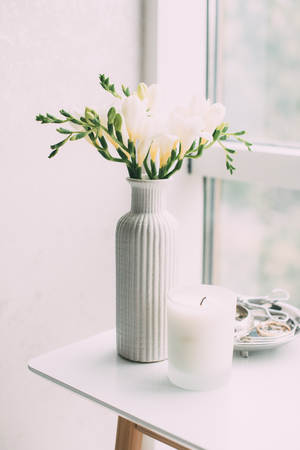 Bouquet of white freesias in vase and aromatic candle on table by the window, elegant home decoration