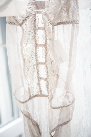 Elegant lacy lingerie on hanger in backlight, lace clothes detal